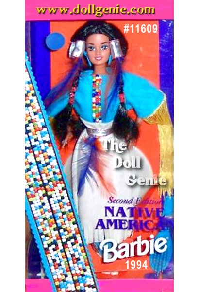 Native American Barbie doll prepares for a traditional powwow ceremony. Her long dress, inspired by the original Native American buckskin dresses, is accented with a silvery-colored belt, long, colorful fringe, and a gorgeous multi-colored bodice. Feathers complement this beautiful ensemble, both on her dress, and intertwined in her dark braided hair.