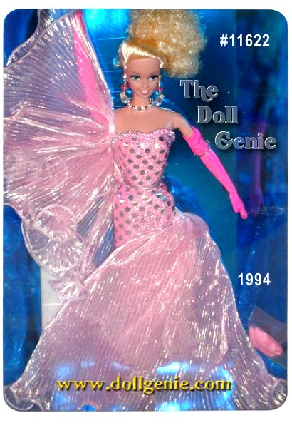 In a sleek strapless pink sheath gown and swirling pink iridescent wrap, Barbie doll makes her entrance. What a stunning vision of sophisticated elegance! Her dress features silvery dots, and accessories include pink opera-length gloves, dangling pink and clear crystal beaded earrings, and a beaded choker. Her blond hair is upswept into an alluring wave of golden locks.