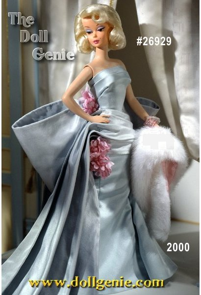 Delphine Barbie doll embodies the ultimate expression of style and elegance in a strapless evening gown in pale turquoise taffeta with a dramatic bow, draped train, and delicate pink flower accents. Her white faux fur stole lined in pink satin gives her stunning ensemble the final glamorous touch.