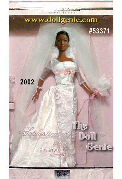 African American Collector Wearing a floor-length gown with a satin bodice and slim skirt of ivory jacquard with rna matching train, Barbie doll looks positively enchanting! Her golden blond hair is styled into an elegant upsweep, topped by her long veil with a pale pink bow at the crown. Soft makeup and a  bouquet of lilies add the fabulous finishing touches. African American Version