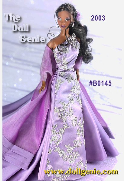 African American Barbie 2003 wears a lavender gown that goes over one shoulder to create an elegant look. The bodice of the gown has shiny, silvery caviar beading. She also wears a dark lavender organza floor length wrap trimmed at the bottom with taffeta. Her hair is pulled back into an elegant low ponytail that is curled on the bottom. She wears silvery flower dangle earrings. Her rhinestone brooch reading 2003 is on the shoulder of the gown.