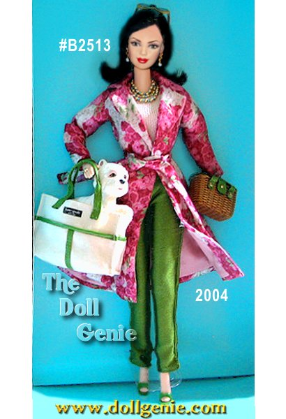 Barbie doll is dressed in an outfit that reflects Kates personal style. The doll wears a floral print coat with three-quarter length sleeves, belted at the waist. Beneath the coat is an ivory knit sweater and green shantung cigarette pants. A faux wicker handbag with golden detail is reminiscent of Kates handbag designs, specifically the Venice Basket. Barbie also carries a canvas tote trimmed with faux green leather. The dog perched at the edge of the bag is modeled after Kates friendly and loyal dog. Barbie wears many striking accessories including bold beaded necklace and earring set with faux turquoise accents, oversized sunglasses, and green high-heel sandals.
