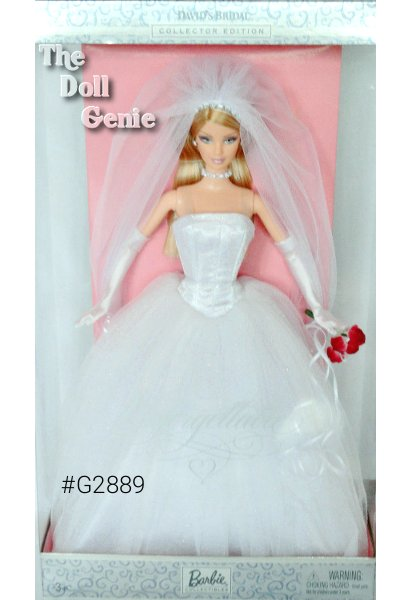 Davids Bridal Unforgettable Blonde Barbie doll wears a beautiful bridal gown with a white glitter-print satiny bodice and a full, glittery tulle skirt. Exceptional accessories include a tulle veil with faux rhinestone tiara attached, faux rhinestone necklace, silvery earrings, red bouquet, white charmeuse gloves, and white high-heel sandals. Say I do! to this exquisite doll! This doll is the Blonde Version.