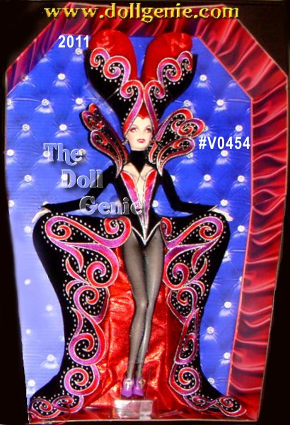 When the sun sinks below the horizon, darkness falls and a fabulous creature of the night arises! Countess Dracula Barbie doll, designed by Bob Mackie satisfies her hunger for high fashion with this over-the-top outrageous outfit! Her vibrant purple gown is accented in orange, black and silver, and features elaborate embroidery and a stand-up collar that frames her face and shows off her bright red hair. From the top of her elaborate headdress all the way down to her purple pumps, she is fiercely fabulous and ready to partake of the vibrant nightlife! Less than 3,200 worldwide