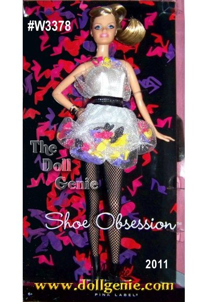 The 2012 Shoe Obsession Barbie Doll #W3378 is a true fashionista. Barbie can never have enough shoes. This whimsical dress celebrates that fashion heritage with 50 shoes sewn into its structure. A tulle overlay is gathered into pockets to hold classic Barbie mules in yellow, purple, black and pink (of course!). The pale gray dress is complemented by black fishnets and a cute pair of black ankle boots for a fun and fanciful look. A necklace with matching shoe icons completes the outfit while making a statement about Barbie dolls love of shoes - they are her favorite fashion accessory!